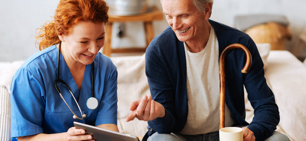 female nurse and senior man are laughing while watching at the tablet device