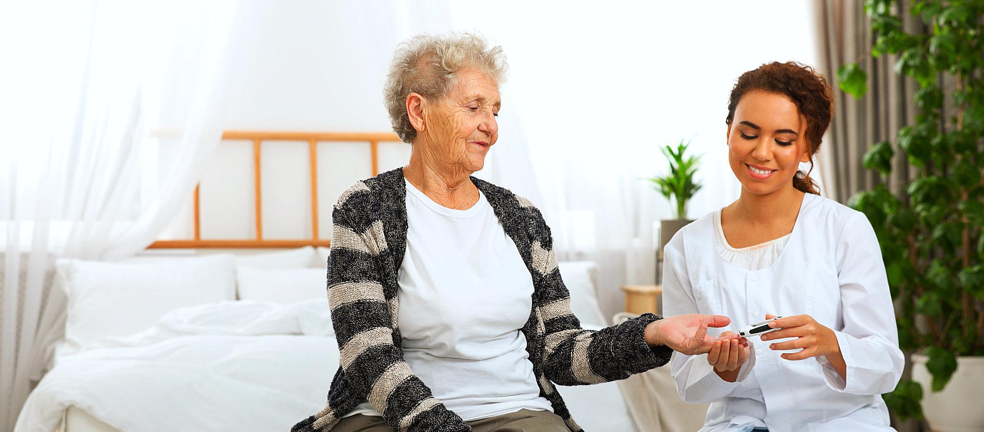 caregiver monitoring the sugar level of senior woman