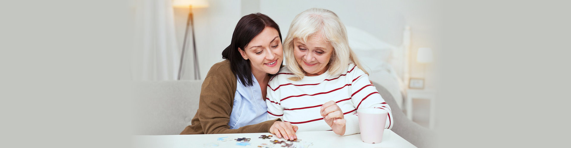 caregiver and senior woman solving a puzzle