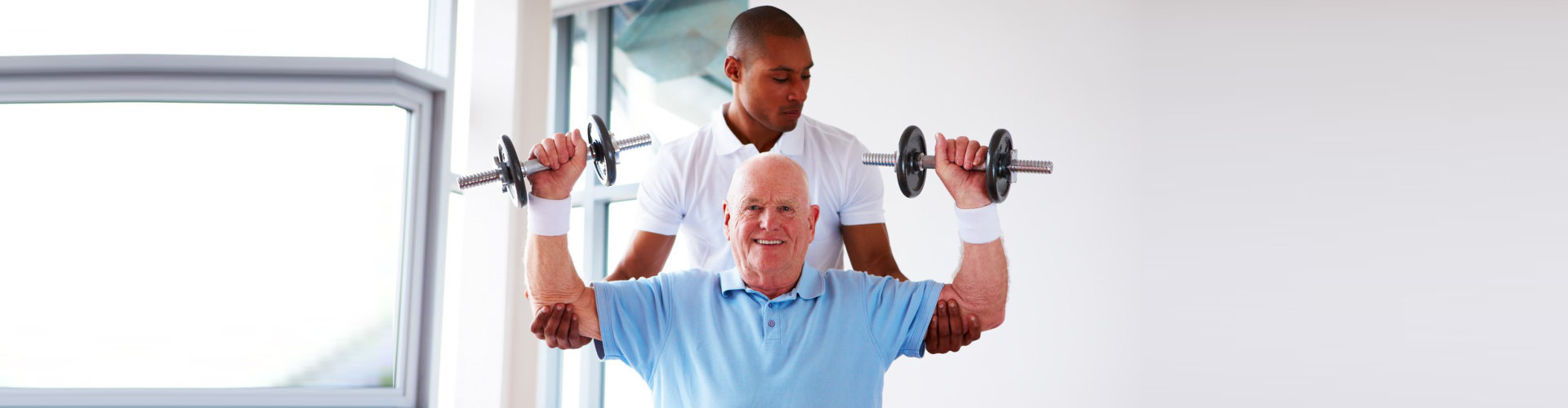 gym instructor assisting senior man doing an exercise